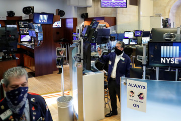 Traders wearing masks watch as the Opening Bell rings, on the first day of in-person trading since the closure during the outbreak of the coronavirus disease (COVID-19) on the floor at the NYSE in New York