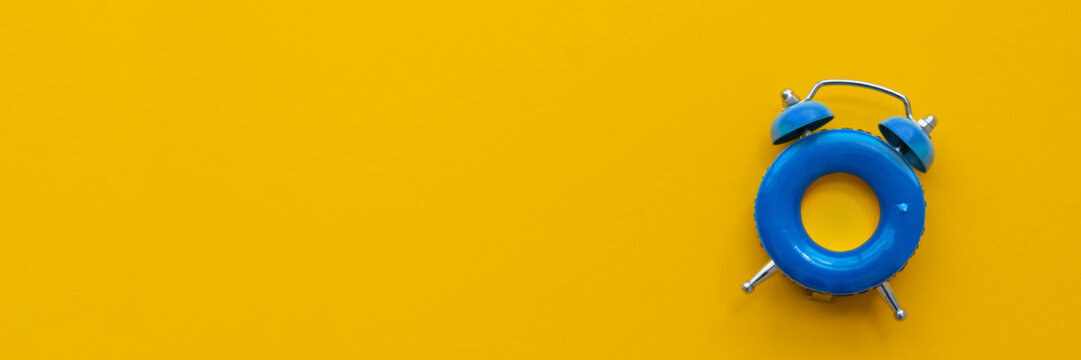 Banner 3:1. Vacation time. Blue alarm clock as swimming ring form on yellow background. Top view. Copy space