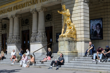 People enjoy the sunny weather sitting on the stairs of The Royal Dramatic Theatre in Stockholm