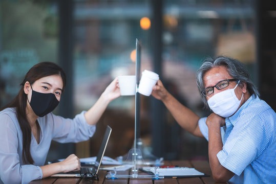 Asian business woman working in cafe with medical face mask and table shield, social distancing of the new normal lifestyle after epidemic of coronavirus COVID-19
