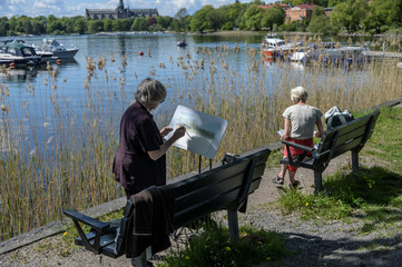 Two women paint as they enjoy the sunny weather at Djurgarden in Stockholm