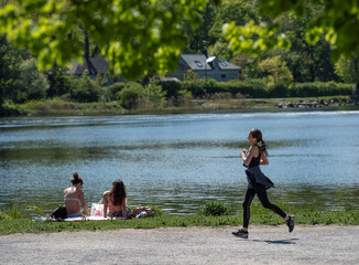 Woman jogs past sunbathers next to a canal at Djurgarden in Stockholm