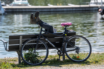 Man has his bicycle parked as he takes a rest enjoying the sunny weather next to a canal at Djurgarden in Stockholm