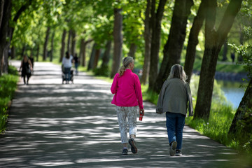 People take a walk in the sunny weather along a canal at Djurgarden in Stockholm