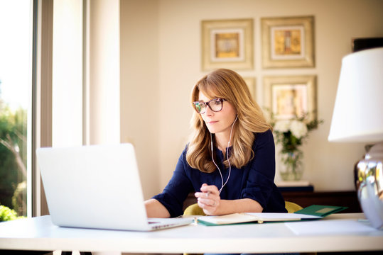 Shot of woman sitting behind her laptop and working from home