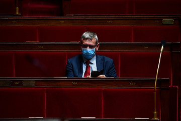 French member of parliament of the Socialist Party (PS) Joel Aviragnet wears a face mask as he attends a session of questions to the Government at the French National Assembly in Paris