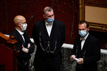 Stewards wearing face masks attend a  session of questions to the Government at the French National Assembly in Paris