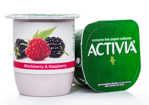 LONDON, UK - AUGUST 18, 2019: Cup of Activia exclusive live yogurt cultures with summer berries on white. Product by Danone