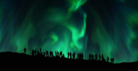 Silhouettes of people under the green northern lights