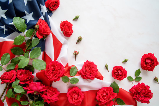 Red roses over the USA flag top view flat lay