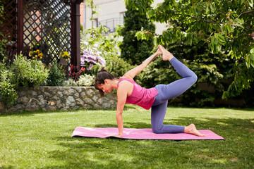 Young attractive slim caucasian brunette kneeling in Half bow yoga posture. Backyard exterior.