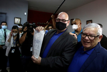 Rodrigo Campos shows the marriage certificate next to his partner Marcos Castillo during their marriage ceremony, after Costa Rica legalised same-sex marriage, in San Jose