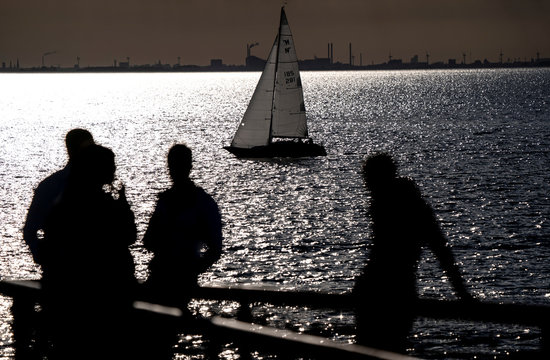 People enjoy the warm evening as a sailing boat passes in Malmo