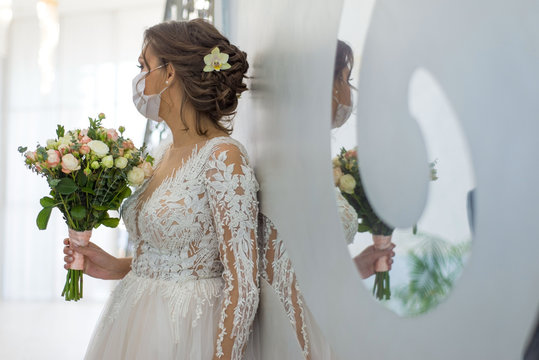 wedding and coronavirus covid 19-20. The bride in a protective medical mask, and a wedding dress, stands in defocus blur, holding a wedding bouquet, reflected in the mirror of the wedding