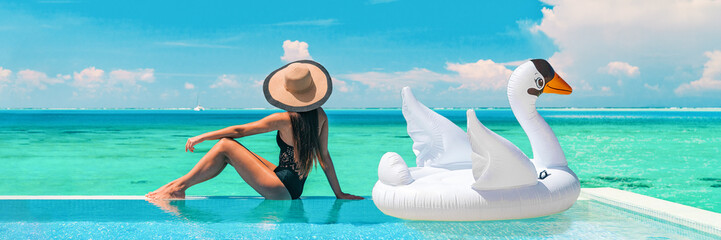 Luxury swimming pool vacation travel lady sun tanning relaxing on infinity ocean waterfront resort with floating white swan inflatable toy float banner panoramic summer background.