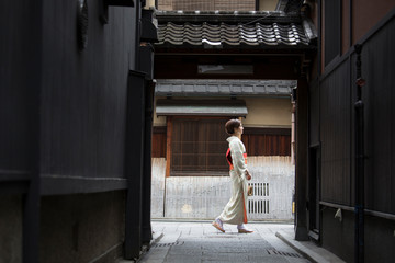 Young Japanese woman in kimono walking on the street