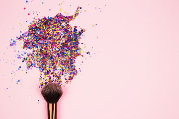Closeup of professional cosmetic makeup brush with explosion of shiny colorful sparkles on bright pink background with copyspace for your text. Creative make-up concept