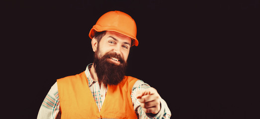 Man builders, industry. Builder in hard hat, foreman or repairman in the helmet. Bearded man worker with beard in building helmet or hard hat. Portrait of a builder smiling. Face closeup