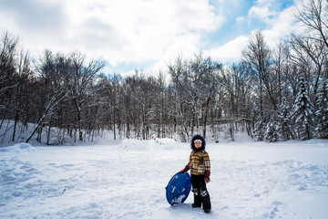 Boy standing in the snow with his sledge, USA