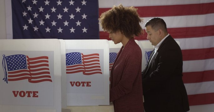 Profile, medium shot, young mixed-race woman and Hispanic man in polling station, voting in a booth with US flag in background.