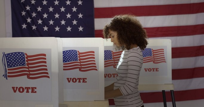 Profile, medium shot, young Hispanic woman in polling station, voting in a booth with US flag in background.