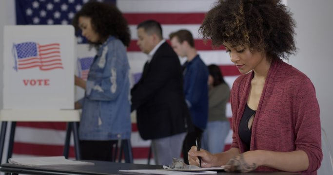 MS Young mixed-race woman staffing desk at polling station with various voters in background, US flag on wall behind them.