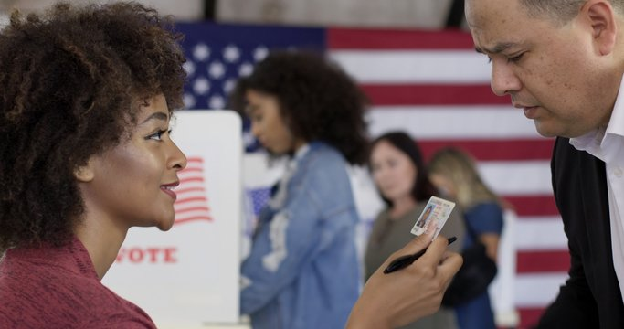 CU Mixed-race staff person inspects photo ID, driving license, presented by Hispanic man at US polling station. Other voters soft focus in background with US flag