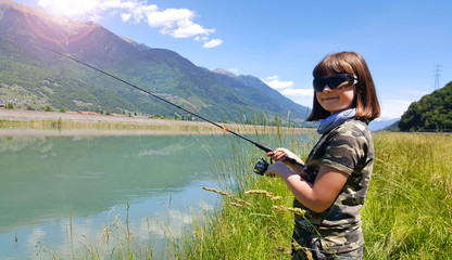 young girl is fishing trout in the river