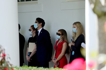 Staff members in masks listen as U.S. President Trump speaks about negotiations with pharmaceutical companies over the cost of insulin, at the White House in Washington