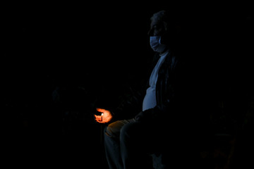 A man wearing a protective face mask holds a candle as he attends an Easter service open to the public in Constanta