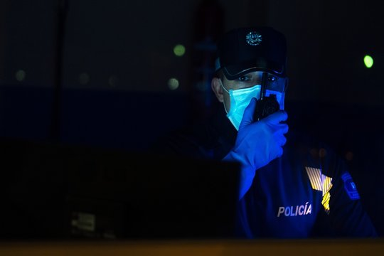 Closeup shot of an adult police officer talking on the radio wearing mask and gloves at night