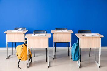 Modern school desks near color wall