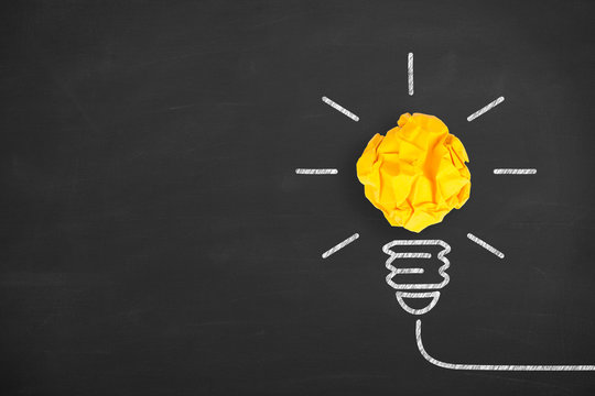Creative Idea Concepts Light Bulb with Crumpled Paper on Chalkboard Background