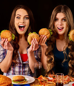 Group women eat best hamburger and pizza in burger bar . Friends take fast food drink cola and chatting.
