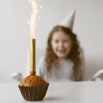 Candle fountain burns brightly on a holiday cupcake. Little girl s birthday. Concept party in honor of children's holiday.