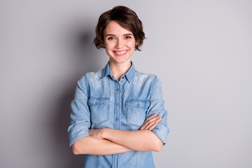 Photo of attractive business lady wavy bobbed hairdo arms crossed self-confident chief worker beaming white teeth smile wear casual denim shirt isolated grey color background