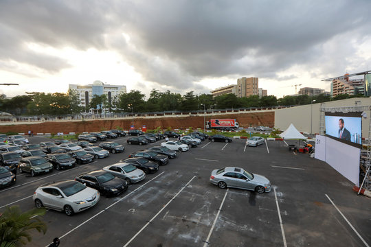 """Movie audiences sit in their parked cars as they watch """"Living in bondage"""" at a drive-in cinema, following the relaxation of lockdown, amid the coronavirus disease (COVID-19) outbreak in Abuja"""