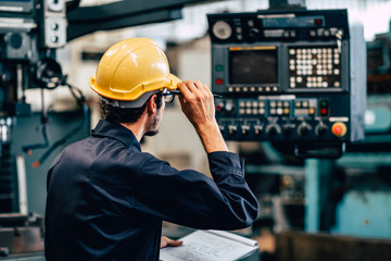 Fototapeta Young American worker intend to work in a heavy industrial factory looking and control machine in production line. obraz