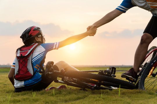 Woman riding mountain bike was accident crashed and fell to the grass while a lover her coming in to help at the beautiful sunset time. Using help and giving family love concept.