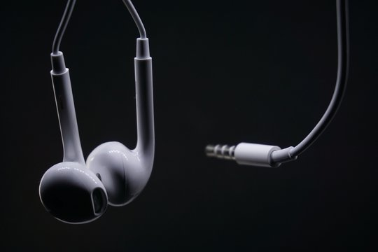 White earphone with black background. Earphone and audio jack with black background.