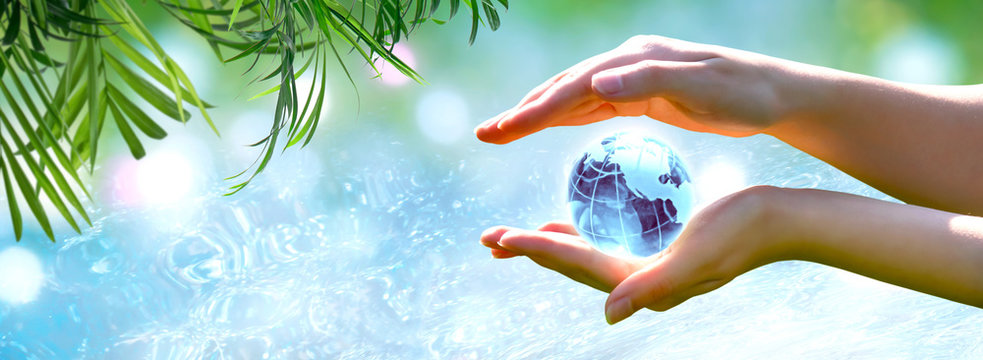 Card for World Oceans Day or Water Day. Blue planet crystal glass globe in human hand on pure sea background. Saving environment, save, protect clean planet and ecology, sustainable lifestyle concept.