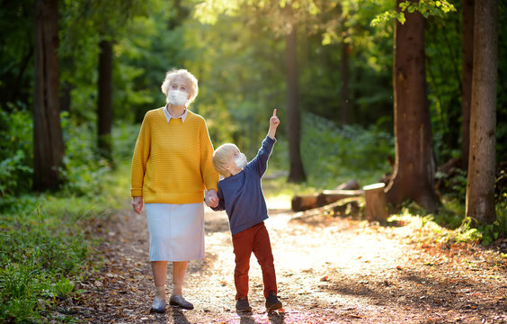 Elderly grandmother and little grandchild wearing facemask walking together in sunny summer park. Grandma and grandson. Lifting virus lockdown orders. Social distancing.