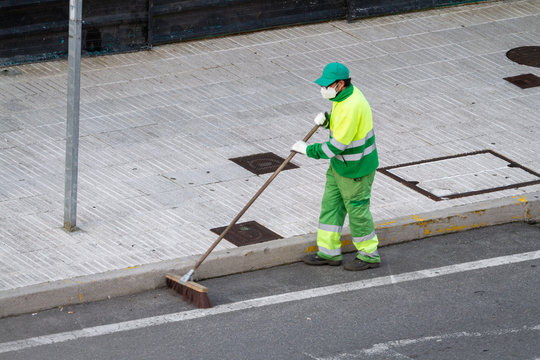Street sweeper wearing face mask working on a sidewalk. Public cleaning concept during coronavirus pandemic