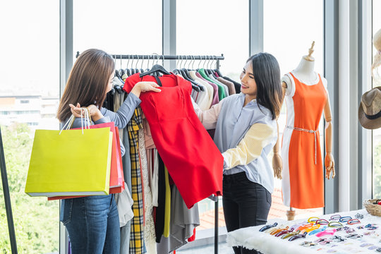 Sale woman showing a red dress to a woman shopper holding shopping bags at a clothing fashion shop.