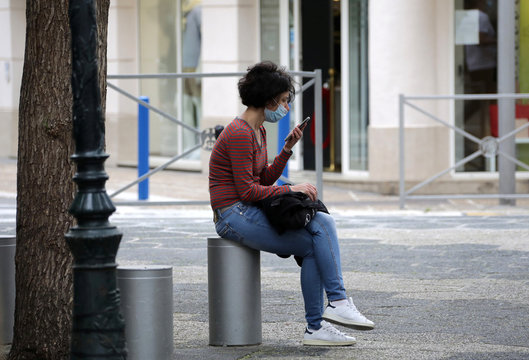 A woman, wearing a protective face mask, looks at her mobile phone in Nice