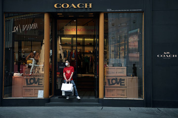 Man wearing a protective mask stands outside a Coach store, amid the coronavirus disease (COVID-19) outbreak in Kuala Lumpur