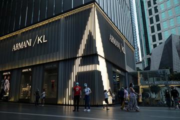 Shoppers wearing protective masks pass by a Giorgio Armani store, amid the coronavirus disease (COVID-19) outbreak in Kuala Lumpur