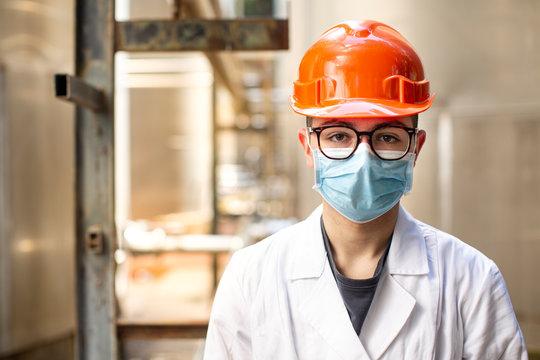 Tecnico specialista in camice bianco e caschetto protettivo arancione indossa una mascherina chirurgica e degli occhiali tecnici , in contesto industriale.