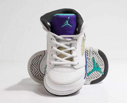 london, england, 05/05/202 White, purple and aqua, nike air baby jordan 4 model retro trainers, for kiddies and toddlers. Air jordan basketball sneakers. Fashionable retro style street fashion.