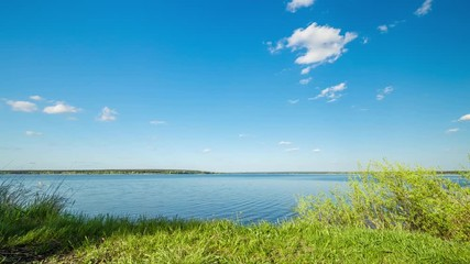 Fototapete - Summer landscape with lake, blue sky and clouds. Nature wilderness 4k time lapse. Countryside outdoors, relaxation, space scenic. Beautiful pond, forest, green meadow, with reflection in water.